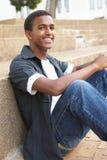 Lächelnder männlicher Jugendkursteilnehmer, der draußen sitzt Stockfoto
