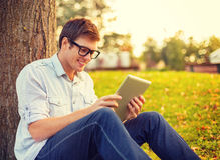 Lächelnder männlicher Student in den Brillen mit Tabletten-PC Lizenzfreies Stockfoto