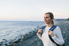 Lächelnder Reisender der jungen Frau in einer weißen Kleidung, die auf dem Ufer und den Blicken in Meer steht Stockbild