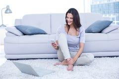 Lächelnder schöner Brunette, der auf dem Boden und der Anwendung ihres Telefons sitzt Stockfotos