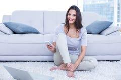 Lächelnder schöner Brunette, der auf dem Boden und der Anwendung ihres Telefons sitzt Lizenzfreies Stockbild