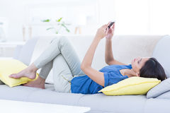 Lächelnder schöner Brunette, der auf der Couch und der Anwendung ihres Telefons sich entspannt Lizenzfreies Stockbild