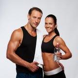 Lächelnder sportlicher Mann und Frau mit Flasche Stockbilder