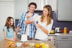 Lächelnder strömender Fruchtsaft der Mutter im Glas mit Familie Stockfotografie