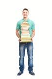 Lächelnder Student, der großen Stapel Bücher hält Lizenzfreie Stockbilder