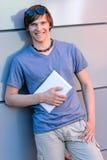 Lächelnder Studentenjunge, der an der modernen Wand sich lehnt Stockfotos