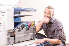 Lächelnder Techniker, der nahe Kopierer sitzt Stockfoto