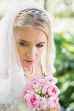 Lächelnder tragender Schleier der Braut, der den Blumenstrauß unten schaut hält Stockfoto