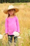 Lächelnder tragender westlicher Hut des Strohs des kleinen Mädchens. Stockbild