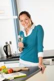 Lächelnder trinkender Wein der Frauenküche, der Gemüse vorbereitet Stockbilder