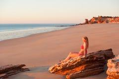 Lächelnder tropischer Strandsonnenuntergang der jungen Frau Stockfoto
