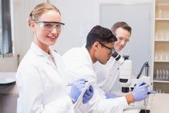 Lächelnder Wissenschaftler, der Kamera während Kollegen arbeiten mit Mikroskop betrachtet Stockfotografie