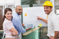 Lächelndes Architektenteam, das zusammen unter Verwendung der Tablette gedanklich löst Lizenzfreie Stockfotos