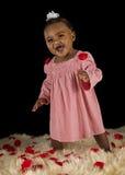 Lächelndes Baby abgedeckt mit rosafarbenen Pedalen Stockfoto
