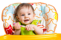 Lächelndes Baby mit Löffel Stockfoto