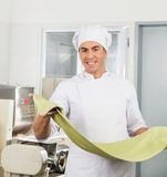 Lächelndes Chef-Processing Spaghetti Pasta-Blatt Lizenzfreie Stockfotos