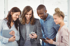 Lächelndes Geschäftsteam unter Verwendung der Technologie Stockfoto