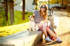 Lächelndes Hippie-Mädchen mit ihrem Hund und Fahrrad Stockfotografie