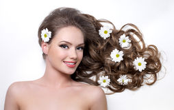 Lächelndes jugendlich Mädchen mit Blume im Haar Stockfotos