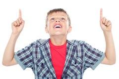 Lächelndes junges Kind, das oben und Zeigen schaut Stockfoto