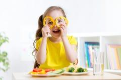 Lächelndes Kind, das im Kindergarten isst Stockfotografie