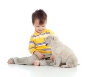 Lächelndes Kind, das mit einem Welpen spielt Stockfotos