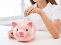 Lächelndes Kind, das Münze in großes Sparschwein setzt Lizenzfreie Stockfotografie
