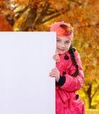 Lächelndes Kind des kleinen Mädchens im Herbst kleidet den Jackenmantel und -hut, die ein weißes Brett der leeren Anschlagtafelfa Stockbild