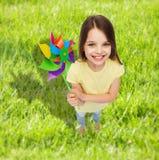 Lächelndes Kind mit buntem Windmühlenspielzeug Lizenzfreie Stockbilder