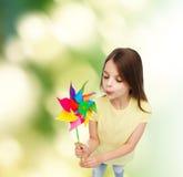 Lächelndes Kind mit buntem Windmühlenspielzeug Stockfotografie