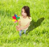 Lächelndes Kind mit buntem Windmühlenspielzeug Stockbild