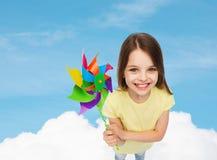 Lächelndes Kind mit buntem Windmühlenspielzeug Lizenzfreies Stockbild