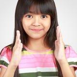 Lächelndes kleines asiatisches Mädchen zeigen offenen Raum zwischen ihrer Hand Stockfotos
