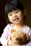 Lächelndes kleines Kind mit einem Teddybären Stockbild