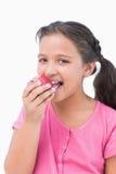 Lächelndes kleines Mädchen, das Apfel isst Stockbild