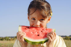 Lächelndes kleines Mädchen, das Wassermelone isst Stockbild