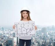 Lächelndes kleines Mädchen im Sturzhelm, der Plan zeigt Stockfotos