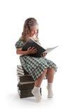 Lächelndes kleines Mädchen mit Zöpfen ein Buch lesend Stockbild