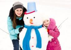 Lächelndes kleines Mädchen und junge Frau mit Schneemann am Wintertag Stockfotografie