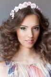 Lächelndes leichtes elegantes junges schönes Mädchen mit dem üppigen Haar mit einer Kante von hellen Farben Lizenzfreie Stockfotos