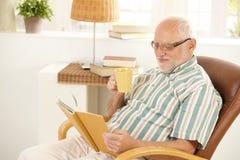 Lächelndes älteres mit Buch und Tee zu Hause sich entspannen Stockbild