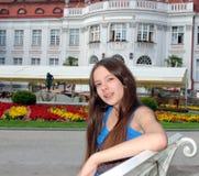 Lächelndes Mädchen, das auf einer Bank sitzt Stockfoto