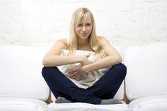Lächelndes Mädchen, das ein Kissen auf weißer Couch streichelt Stockbild