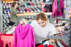 Lächelndes Mädchen, das eine warme Jacke in der Sportboutique vorwählt Stockbild