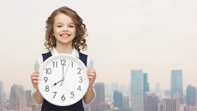 Lächelndes Mädchen, das große Uhr hält Stockbild