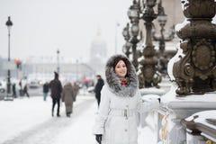 Lächelndes Mädchen, das seltenen schneebedeckten Tag in Paris genießt Stockfotografie