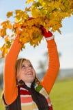 Lächelndes Mädchen, das trockenen Blattherbstbaum auswählt Stockfoto
