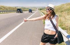 Lächelndes Mädchen des Reisenden fährt entlang einer Landstraße per Anhalter Stockbild