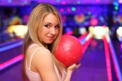 Lächelndes Mädchen mit Kugel steht im Bowlingspielklumpen Stockfotografie
