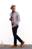 Lächelndes männliches Mode-Modell, das zurück geht und flüchtig blickt Stockfoto